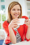 Woman Relaxing At Home With Hot Drink Stock Photo
