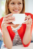 Woman Relaxing At Home With Hot Drink. Sitting Down Looking Away From Camera Royalty Free Stock Photos