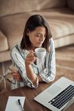 Woman relaxing at home with laptop computer and drinking coffee stock photos
