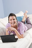 Woman relaxing at home on sofa with laptop Royalty Free Stock Photos