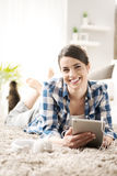 Woman relaxing at home with tablet Stock Images