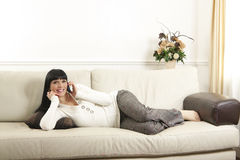 Woman relaxing at home talking on the phone Royalty Free Stock Photos