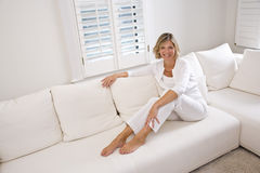Woman relaxing at home on white sofa. Smiling woman relaxing at home in white living room Royalty Free Stock Photo