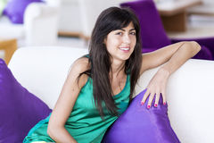 Woman relaxing at home on white sofa with purple pillows Royalty Free Stock Photography