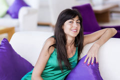 Woman relaxing at home on white sofa with purple pillows Stock Photography