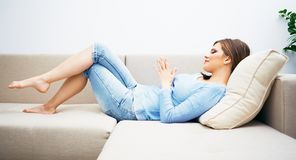 Woman relaxing at home. Young woman lying on sofa Royalty Free Stock Images