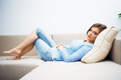 Woman relaxing at home. Young woman lying on sofa Stock Images