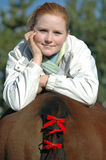 Woman Relaxing on Horse. Pretty woman posing on the rear end of her horse. Horse has red bows in his tail royalty free stock photos