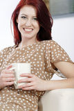 Woman relaxing with hot drink on sofa Stock Images
