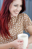 Woman relaxing with hot drink on sofa Stock Photography