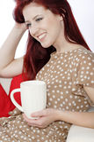 Woman relaxing with hot drink on sofa Stock Photo