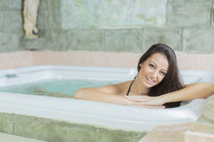 Woman relaxing in the hot tub. Young woman relaxing in the hot tub royalty free stock photos