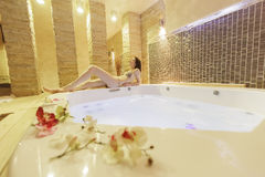 Woman relaxing by the hot tub Royalty Free Stock Image