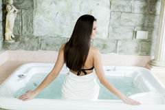 Woman relaxing in the hot tub. Young woman relaxing in the hot tub Royalty Free Stock Image