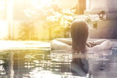 Woman relaxing in hotel spa swimming pool looking at view with sunlight and copy space. Woman relaxing in hotel spa swimming pool looking at view with bright royalty free stock photo