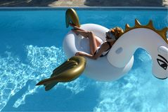 Free Woman Relaxing In Luxury Swimming Pool Resort Hotel On Big Inflatable Unicorn Floating Pegasus Float Royalty Free Stock Photography - 108346777