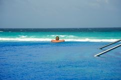 Woman relaxing at an infinity pool Royalty Free Stock Photo