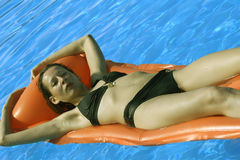 Woman relaxing on an inflatable mattress Royalty Free Stock Image