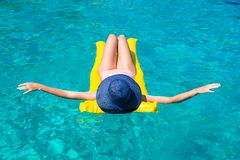 Woman relaxing on inflatable mattress in clear sea Royalty Free Stock Photo