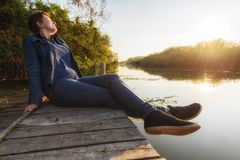 Woman relaxing on jetty Stock Photos