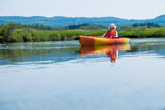 Woman Relaxing on a Kayak and Enjoying her Life. Young Woman Relaxing on a Kayak and Enjoying the Moment of Freedom stock photo