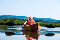 Woman Relaxing on a Kayak and Enjoying her Life. Young Woman Relaxing on a Kayak and Enjoying the Moment of Freedom Royalty Free Stock Image