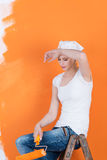 Woman Relaxing On Ladder While Holding Paint Roller Against Wall Royalty Free Stock Photos