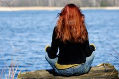 Woman relaxing at the lake. Young woman sitting at lake and relaxing Stock Image