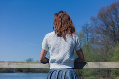 Woman relaxing by lake in forest. A young woman is relaxing by a lake in a forest Stock Photos