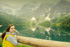 Woman relaxing on the lake and mountains sunny landscape.  Stock Image