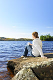 Woman relaxing at lake shore Stock Photos