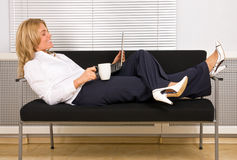 Woman relaxing with laptop on couch drinking coffe Stock Photo