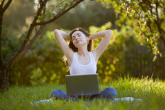 Woman relaxing with laptop outdoors. Woman relaxing with laptop at park Royalty Free Stock Image