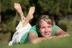 Woman relaxing on a lawn Stock Photography
