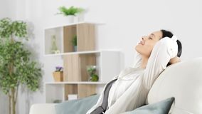 Woman relaxing listening to music at home stock video footage