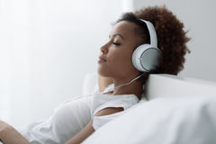 Woman relaxing and listening to music Stock Photography