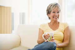 Woman relaxing in living room with coffee smiling Royalty Free Stock Photos