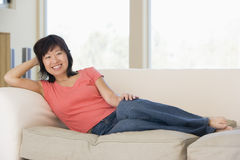 Woman relaxing in living room smiling Stock Photography