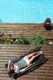Woman relaxing in long chair by the swimming pool Royalty Free Stock Photo