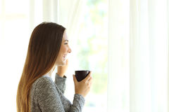 Woman relaxing looking through window at home Stock Photos