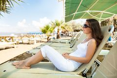 Woman Relaxing On Lounge Chair At Beach Royalty Free Stock Photo