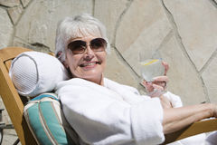Woman Relaxing On Lounge Chair While Holding Glass Of Drink Stock Image