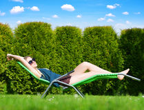 Woman relaxing on lounger. Woman relaxing on lounger in the garden Stock Images