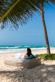 Woman relaxing on a luxurious sunbed on a tropical beach. Woman in a white dress is relaxing on a luxurious sunbed on a tropical beach Stock Image