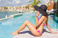 Woman relaxing in luxury resort by the swimming pool Royalty Free Stock Image