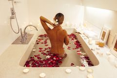 Woman relaxing in bath with candles royalty free stock photos