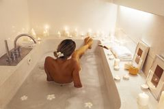 Woman relaxing in bath with candles stock images