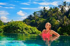 Woman relaxing in luxury spa hotel in infinity swimming pool royalty free stock images
