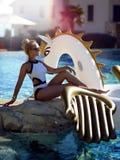 Woman relaxing in luxury swimming pool resort hotel on big inflatable unicorn floating pegasus float. Young fashion woman relaxing in luxury swimming pool resort Royalty Free Stock Images