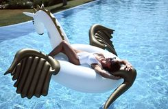 Woman relaxing in luxury swimming pool resort hotel on big inflatable unicorn floating pegasus float. Young fashion woman relaxing in luxury swimming pool resort stock image